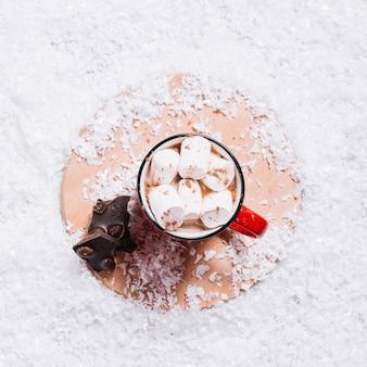 Coupe avec des guimauves près du chocolat sur le stand entre la neige