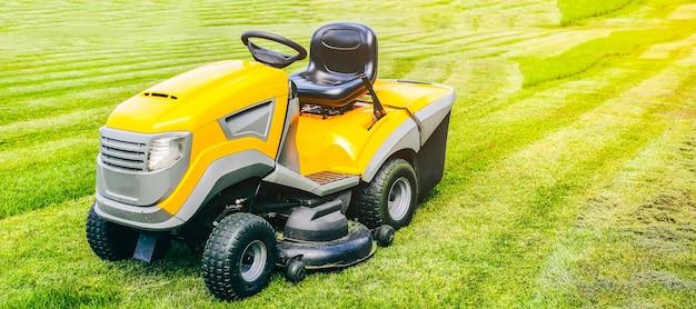Coupe-herbe dans le travail. la machine pour couper la pelouse est debout à l'extérieur. photo lumineuse d'été.
