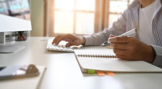 Coupé d'homme d'affaires travaillant avec ordinateur et écrit sur du papier de cahier.