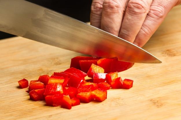 Coupe homme poivron rouge sur une planche de cuisine en bois dans une vue rapprochée