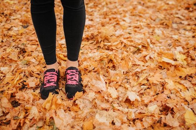 Coupe des jambes de la jeune femme sur les feuilles d'automne. elle a du noir avec des croix roses et un pantalon noir. la femme est seule. elle dans le parc.