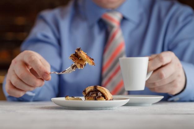 Coupe à la main gâteau au caramel crème sur plaque blanche. sur table en bois