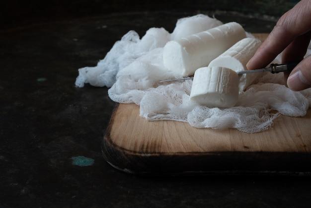 Coupe à la main de l'homme, tranchage, avec couteau fromage de chèvre français, fromage à pâte molle, apéritif traditionnel, collation, dessert sur fond de métal rustique