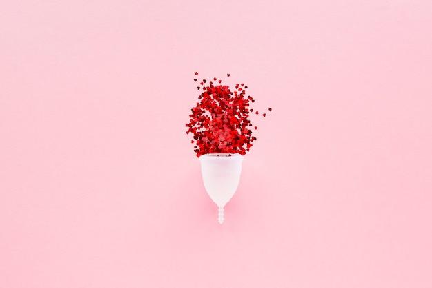 Coupe menstruelle blanche avec des coeurs rouges symbolisant la menstruation sur rose