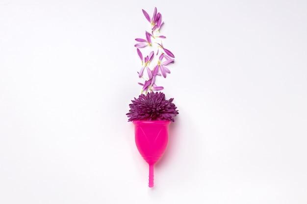 Coupe menstruelle avec des fleurs sur blanc