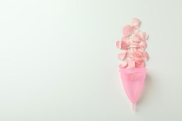 Coupe menstruelle rose avec pétales sur blanc