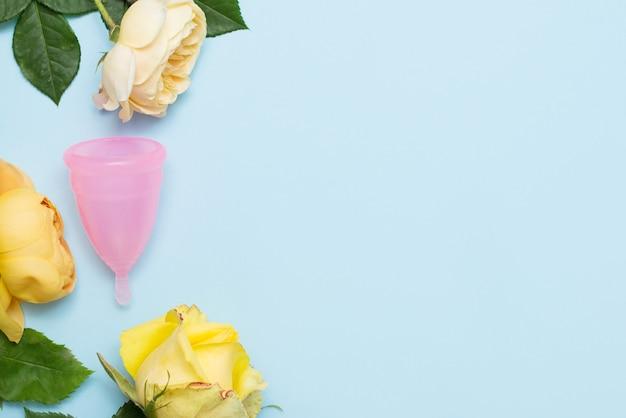 La coupe menstruelle rose se trouve sur le bleu