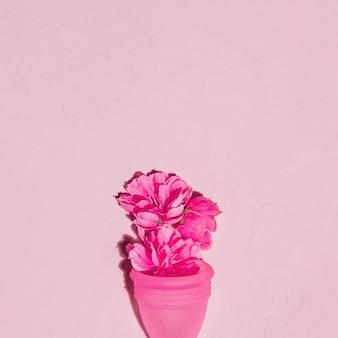 Coupe menstruelle vue de dessus avec des fleurs