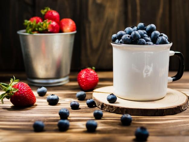 Coupe de myrtille et seau de fraise