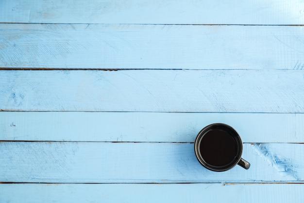 Coupe noire avec boisson sur bois bleu