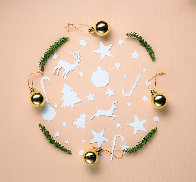 Coupe de papier, boules en or et branche de sapin formant un cercle sur fond de pêche