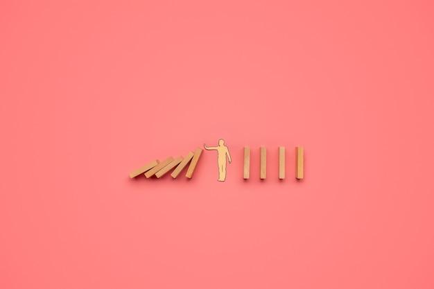 Coupe de papier silhouette d'un homme arrêtant la chute de dominos dans une image conceptuelle.