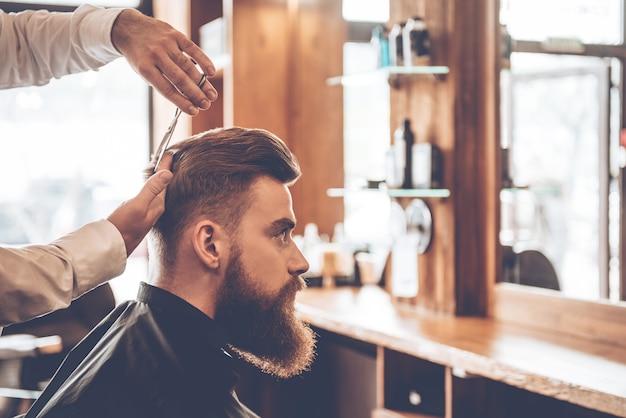 Coupe parfaite de l'arrière vers l'avant. vue latérale rapprochée d'un jeune homme barbu se faisant couper les cheveux par un coiffeur au salon de coiffure