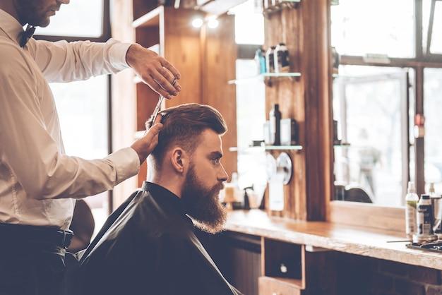 Coupe parfaite. vue latérale rapprochée d'un jeune homme barbu se faisant couper les cheveux par un coiffeur au salon de coiffure