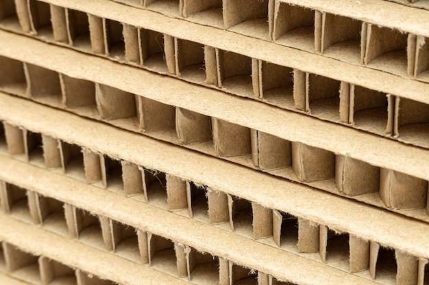 Coupe d'une pile de cartons en nid d'abeille avec gros plan de grandes cellules en arrière-plan