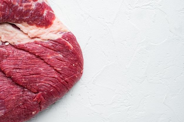 Coupe de poitrine de bœuf crue. ensemble de boeuf black angus, sur table en pierre blanche, vue de dessus à plat
