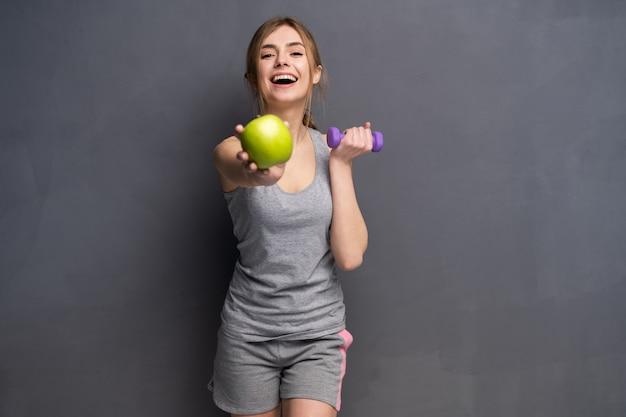Coupe sportive femme tenant des poids d'haltères dans un et pomme dans une autre main