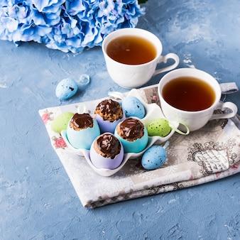 Coupe sucrée de pâques gâteaux treets dans des coquilles d'oeufs colorés sur bleu