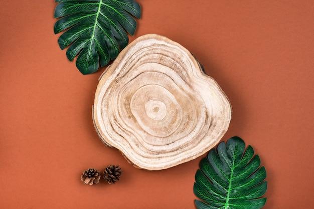 Coupe transversale en bois coupée avec des feuilles de monstera sur une surface brune. vitrine de produits cosmétiques