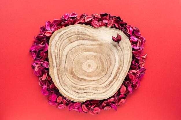 Coupe transversale en bois coupée avec des pétales de fleurs sur une surface rouge comme vitrine pour les produits cosmétiques