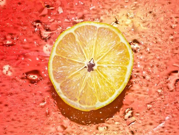 Coupe transversale d'un citron juteux sur fond rouge