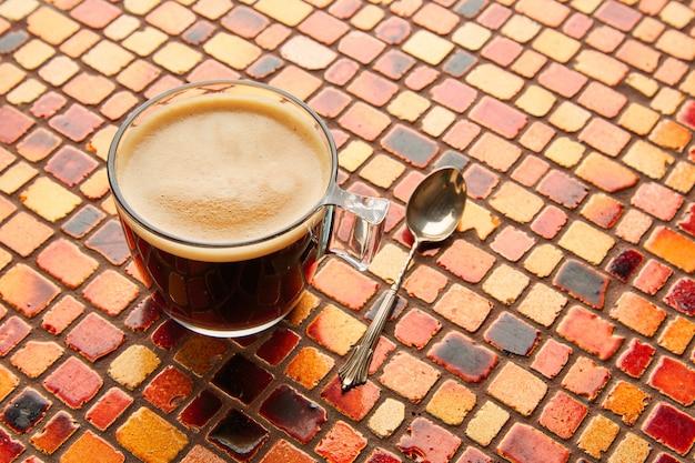 Coupe en verre à café avec de la crème sur une dalle rouge