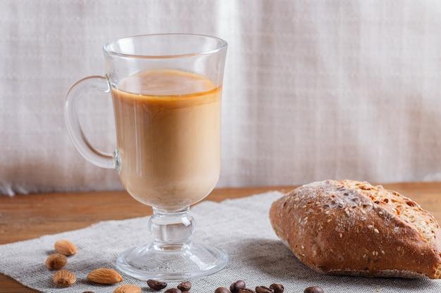 Coupe en verre de café avec de la crème et un pain sur un bois