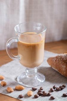 Coupe en verre de café avec crème et pain sur un textile en bois et lin.