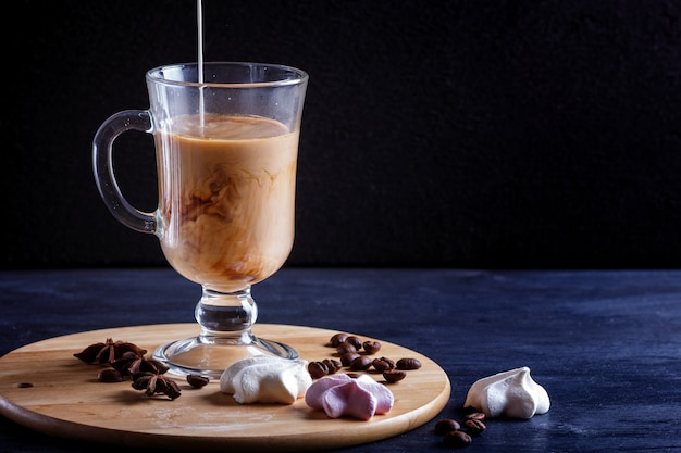 Coupe en verre de café avec de la crème versée et meringues sur une planche de bois sur fond noir