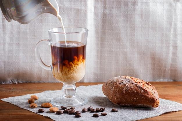 Coupe en verre de café avec de la crème versée et petit pain sur un bois