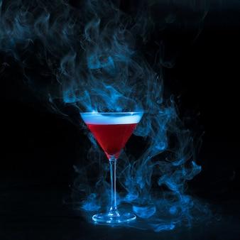 Coupe en verre avec du liquide rouge fumé