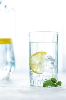 Coupe en verre d'eau, glace, menthe et citron sur une table blanche