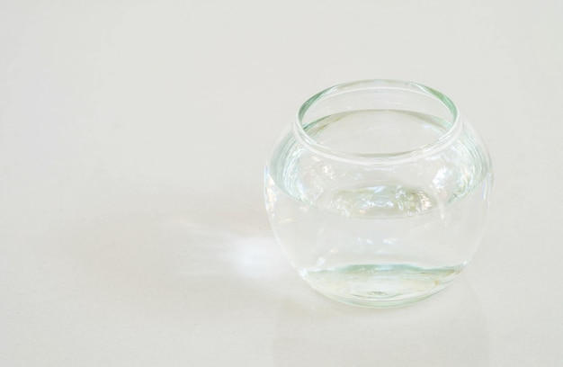Coupe en verre avec de l'eau sur un sol en marbre gris