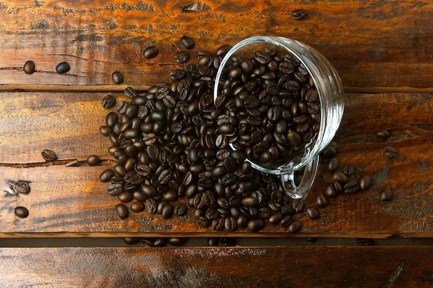 Coupe en verre avec des grains de café torréfiés et frais versé sur une table en bois rustique. vue de dessus