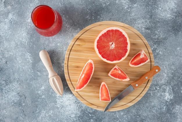 Coupe en verre de jus de pamplemousse frais avec des tranches de fruits et alésoir en bois.