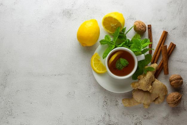 Coupe en verre de thé au gingembre avec des citrons et des feuilles de menthe sur une surface claire,