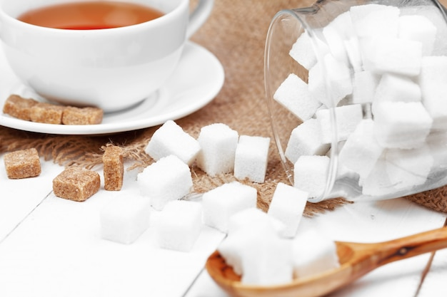 Coupe en verre de thé chaud avec du sucre sur la table