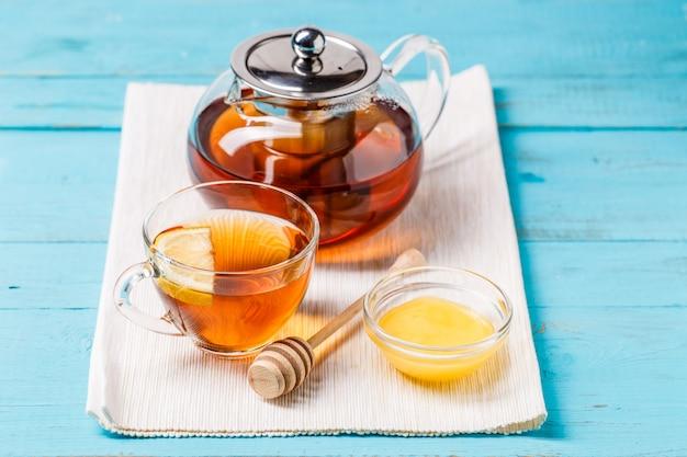 Coupe en verre de thé avec citron, théière en verre et miel.