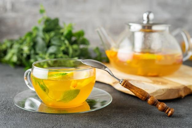 Coupe en verre de thé et théière sur surface grise