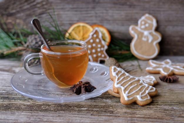Coupe en verre de thé vert et biscuits maison au gingembre frisé sur une table en bois avec des branches de pin, des oranges séchées, de la cannelle, des cônes et des étoiles d'anis