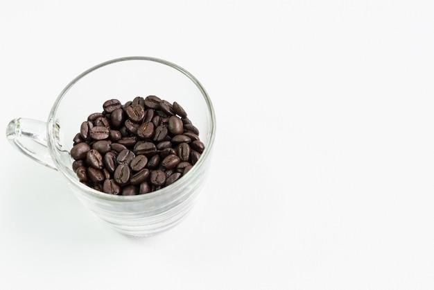 Coupe en verre transparent avec le grain de café foncé.