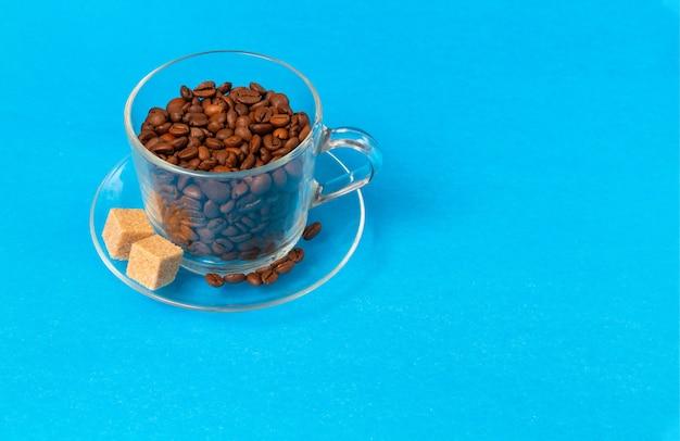 Coupe en verre transparent avec des grains de café avec des tranches de sucre brut sur bleu