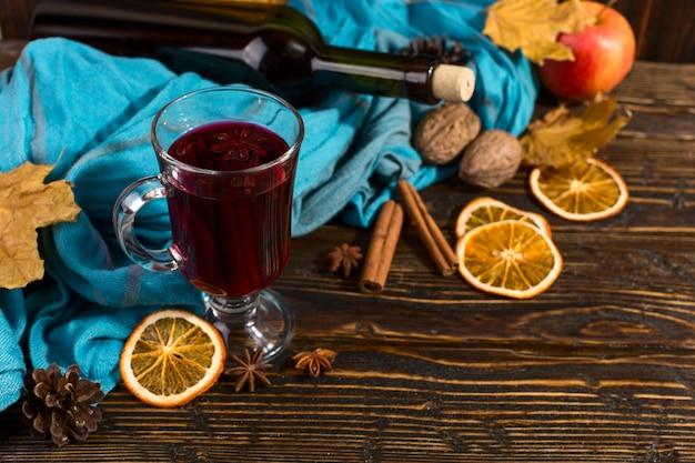 Coupe de vin chaud aux épices, bouteille, foulard, feuilles sèches et oranges sur une table en bois. humeur d'automne, méthode pour garder au chaud dans le froid, fond.