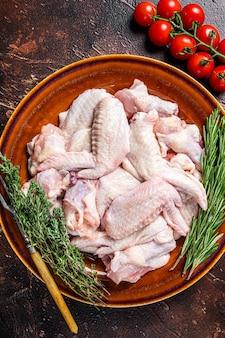Couper les ailes de poulet crues dans une assiette rustique avec du thym et du romarin. fond sombre. vue de dessus.