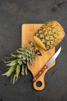 Couper l'ananas frais moelleux juteux sur un bureau en bois et fond gris