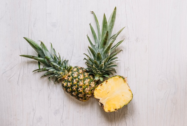 Couper les ananas sur la table blanche