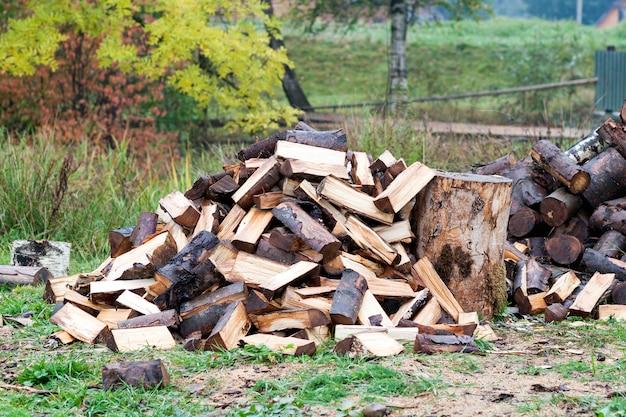 Couper des bûches de bois de chauffage. ressource d'énergie renouvelable. concept environnemental. tas de bois de chauffage haché préparé pour l'hiver, prêt à brûler