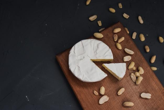 Couper le camembert se trouve sur une assiette de cuisine en bois avec des arachides éparpillées
