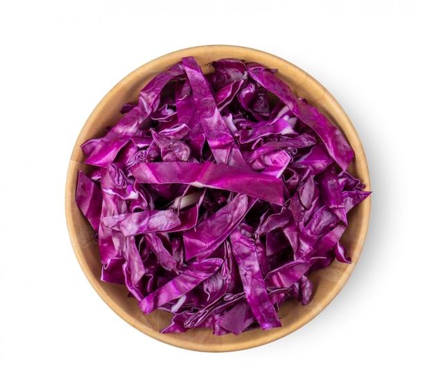 Couper le chou violet dans un bol en bois isolé sur fond blanc. vue de dessus