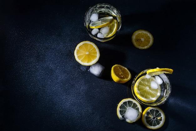Couper les citrons avec des tranches de citron et des glaçons sur un fond sombre. vue de dessus. fermer